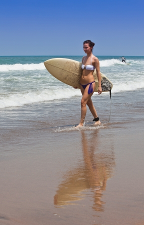 young beautiful girl goes to bikini on an ocean coast with a board for surf photo