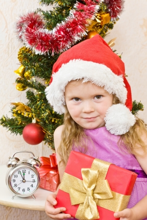 Soon new year! Little girl at a Christmas fir-tree. photo