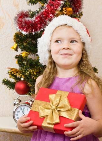 Soon new year! Little girl at a Christmas fir-tree.  photo