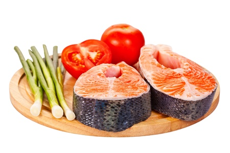 Two raw salmon steaks with tomatoes, lime  and green onion on the cutting board, isolated on white. photo