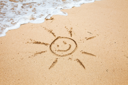 Drawing of the smiling sun on sand