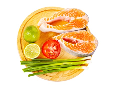 Two raw salmon steaks with a half of lime, red tomatoes and fresh green onion on the cutting board, isolated on white background Stock Photo - 15253870