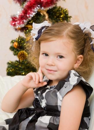 little girl at a Christmas fir-tree. photo
