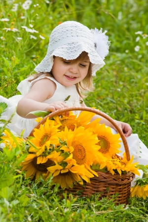 little girl with a big wattled basket with sunflowers photo