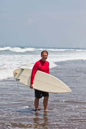 young man goes on an ocean coast with a board for surf Stock Photo - 15890830