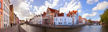 flemish: Old colorful buildings behind the bringe in sunny autumn day
