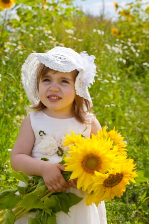 little girl in a dress and a hat and sunflowers photo