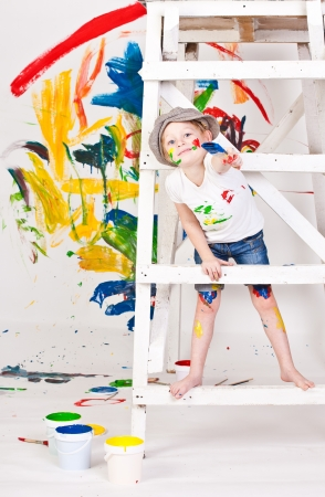 fair haired: girl in a cap with paints Stock Photo