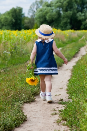 little girl in a dark blue dress goes on a footpath near a field of blossoming sunflowers photo