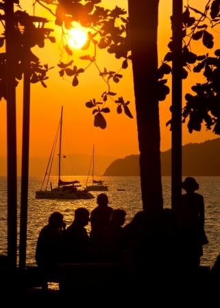 A group of people on the beach looking at the sailing yacht, illuminated by the light of the sun setting Stock Photo - 18573199