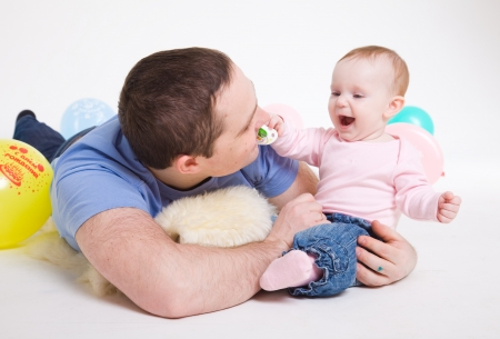 father plays with the eight-monthly daughter  It is isolated on a white background  photo