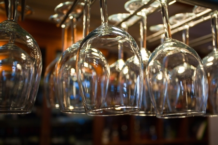 upturned: Many shiny glasses for wine hanging above pub counter