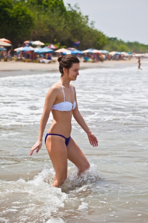 attractive girl in bikini enters into water to bathe at the ocean photo