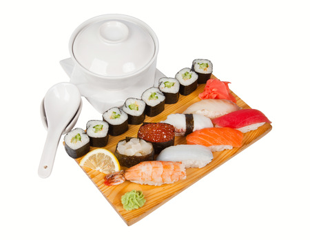Sushi and roll set on wooden board with soup, gari and lemon photo