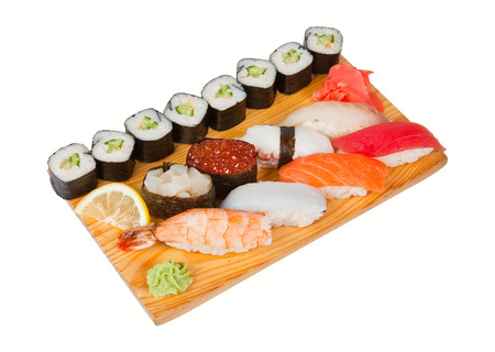 Sushi and roll set on wooden board with gari and lemon photo