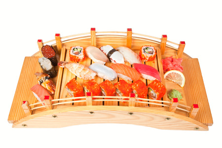 Sushi set with slice of lemon, wasabi and gari on arched wooden plate photo
