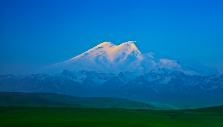 elbrus: Elbrus mountain lit by the rays of the rising sun in the early morning Stock Photo