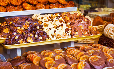 Famous Belgian chocolates and cookies with nuts and raisins on the counter of the store photo