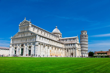 PISA, ITALY - MAY 10, 2014: Tourists on Square of Miracles visiting Leaning Tower in Pisa, Italy. Leaning Tower of Pisa is campanile and is one of the most famous buildings in the world
