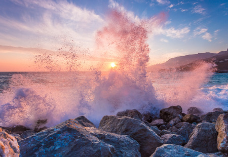 Big sea wave breaks against a stone at sunrise Stock Photo