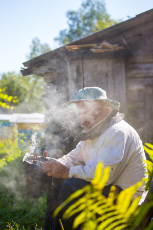 beekeeper prepares the smoker to work  on an apiary