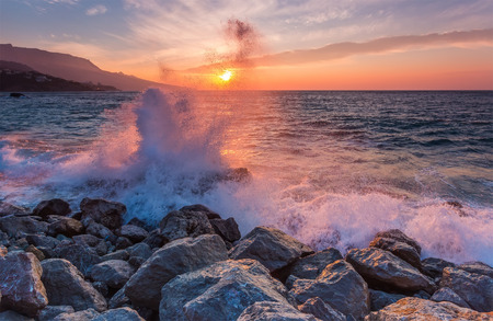 Big sea wave breaks against a stone at sunrise Stock Photo