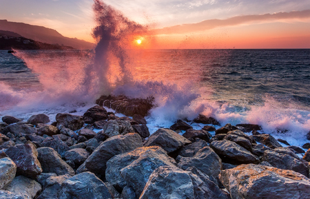 Amazing power of waves crashing against the rocks at dawn Stock Photo