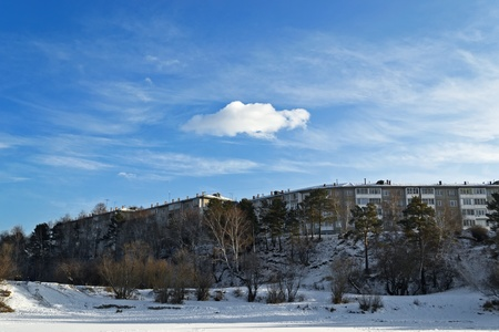 long five-storey panel building on top of a mountain, on a background of trees in the winter. photo