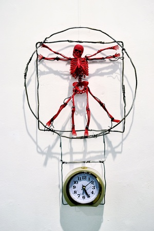 red toy skeleton, which hangs over a mechanical alarm clock - a parody of Leonardo Da Vinci work