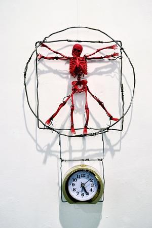 red toy skeleton, which hangs over a mechanical alarm clock - a parody of Leonardo Da Vinci work Stock Photo - 11520849