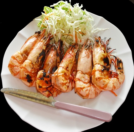 6 baked shrimp, arranged in a row on a plate dressed with a salad. isolated                                photo