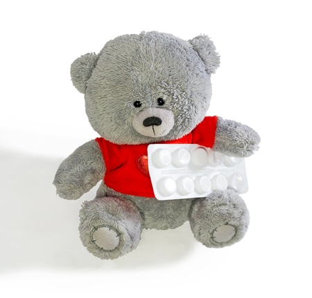 Toy teddy bear holding a white paw pack of tablets. isolation photo