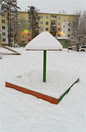 childrens sandbox with a lid, a fungus covered with snow in winter photo