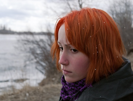 sad redhead girl looking to the side photo