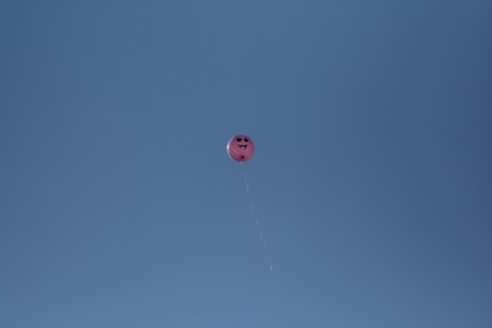 weightless: the balloon flying in the distance with a cheerful smile Stock Photo