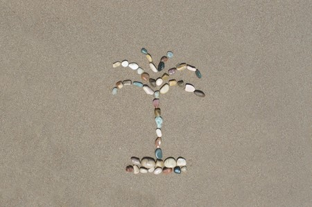 the figure of palm trees on sea sand - a symbol of the holiday, travel and leisure Stock Photo