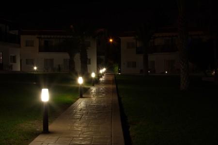 walkway lined with stone lanterns illuminated Stock Photo