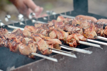 the process of cooking meat on skewers over the coals Stock Photo