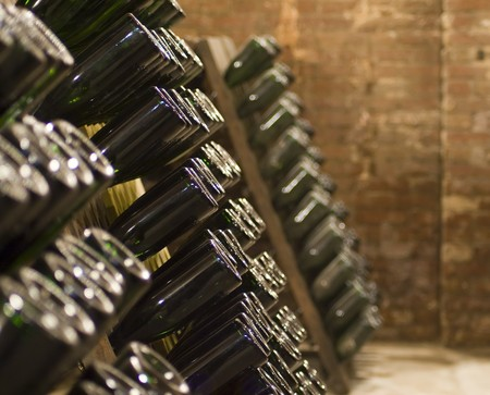 Closeup of bottles of wine aging in an old cellar Stock Photo