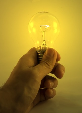 yelllow: A hand holding a yelllow lighted bulb Stock Photo