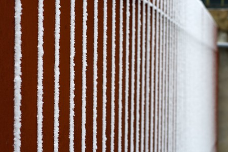 vertical bars: Snow on red vertical bars of an iron fence