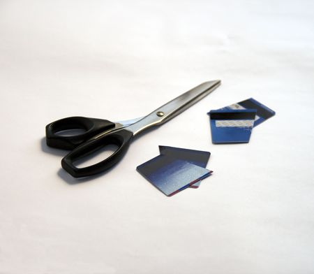 flux: Two cut credit cards and pair of black scissors