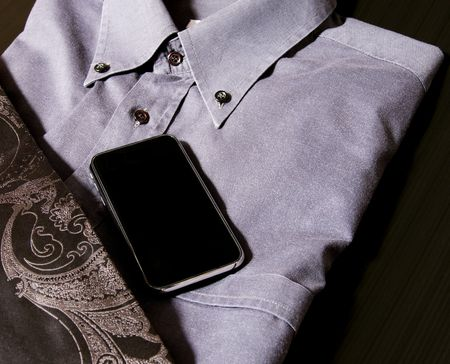 Last generation telephone on a gray shirt and a black tie
