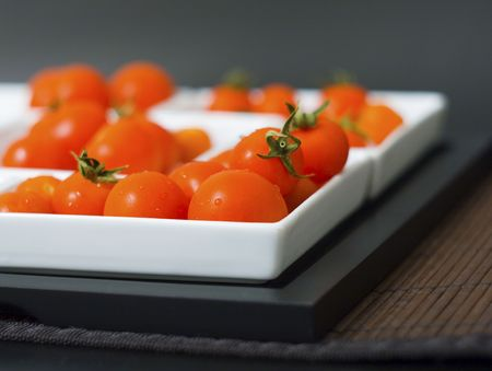 Some little tomatoes in white plates and wooden tablemats