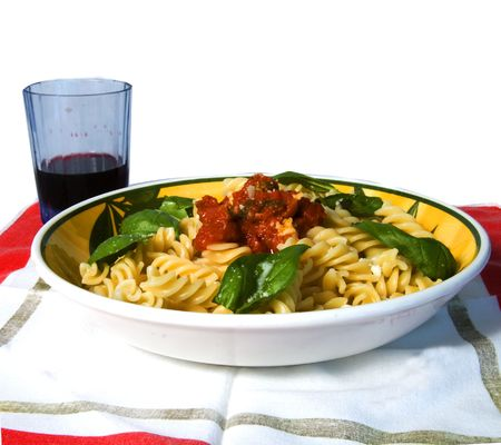 A plate full of italian pasta (fusilli al sugo), over a white background, with a glass of wine on the background Stock Photo