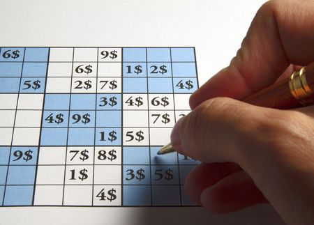 Male man playing sudoku with dollars symbol in it photo
