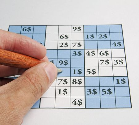 Male hand with a pen over a sudoku with dollar symbols photo