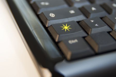 llave de sol: Detalle de las teclas de un teclado de computadora negro: sobre una clave, un sol amarillo Foto de archivo