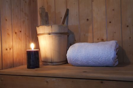 Inside a wooden sauna, towel, candle and bucket