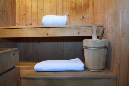 perspire: Inside a wooden sauna, towel, candle and bucket